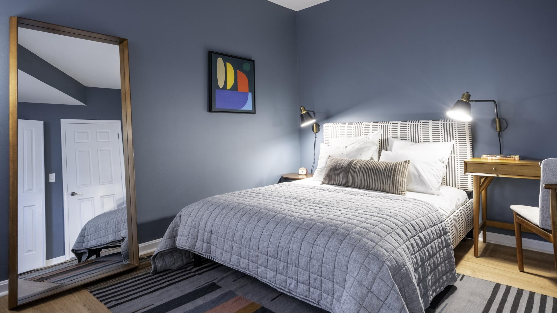 Bedroom of a model apartment at The Ellington with blue walls and a large bed