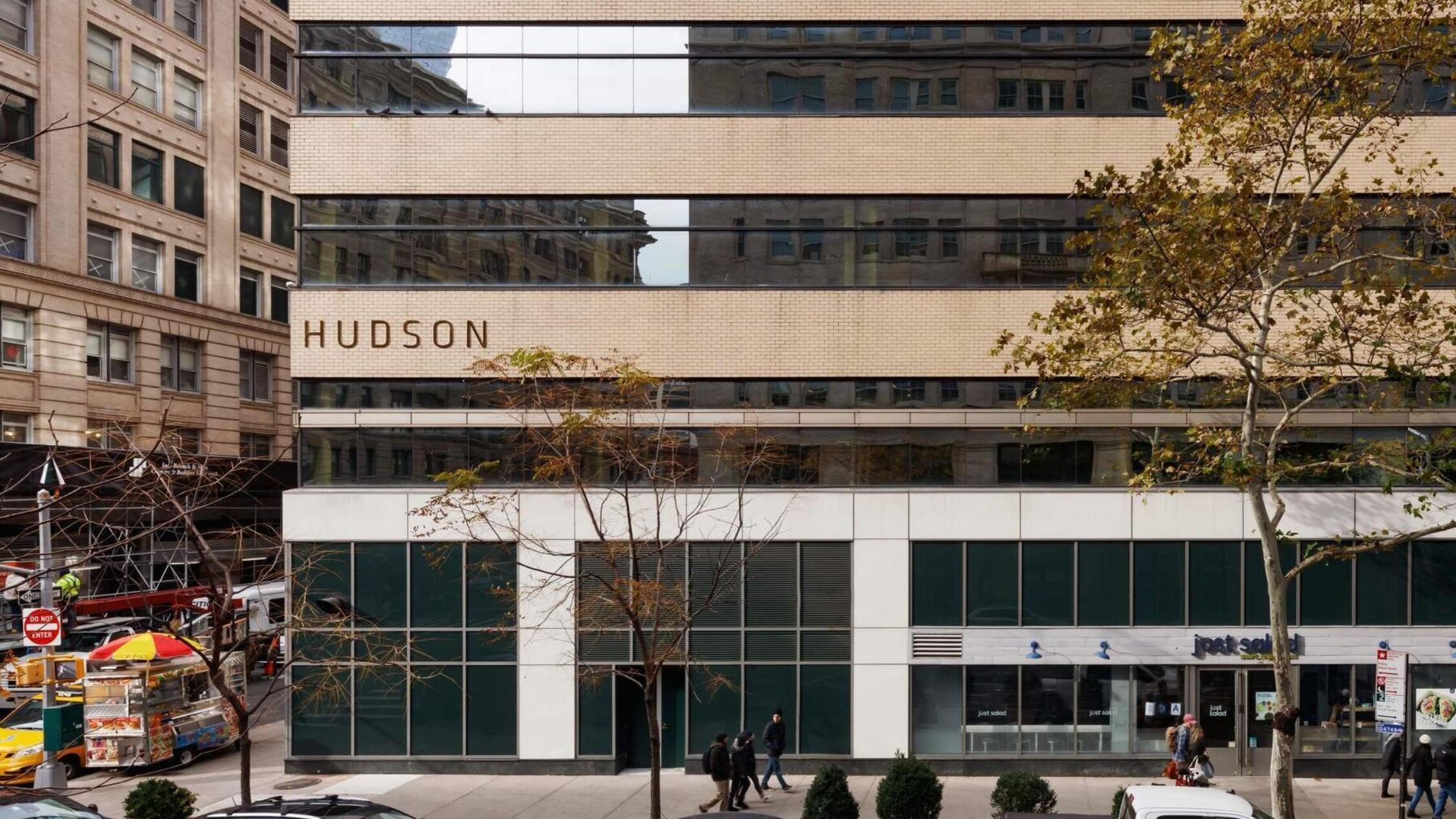 325 Hudson building facade with cars parked on street and pedestrians on sidewalk