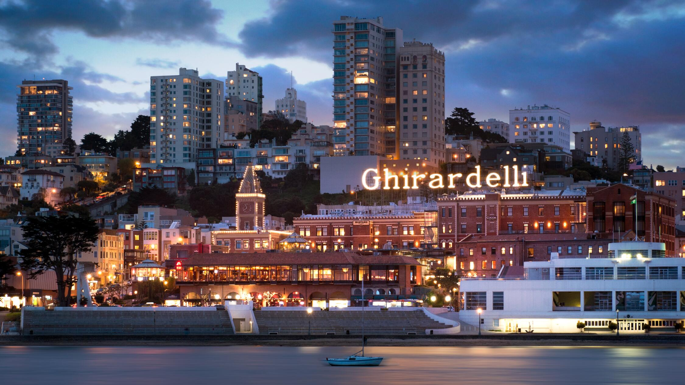 Ghirardelli Square exterior at dusk with bay in foreground and skyline in background