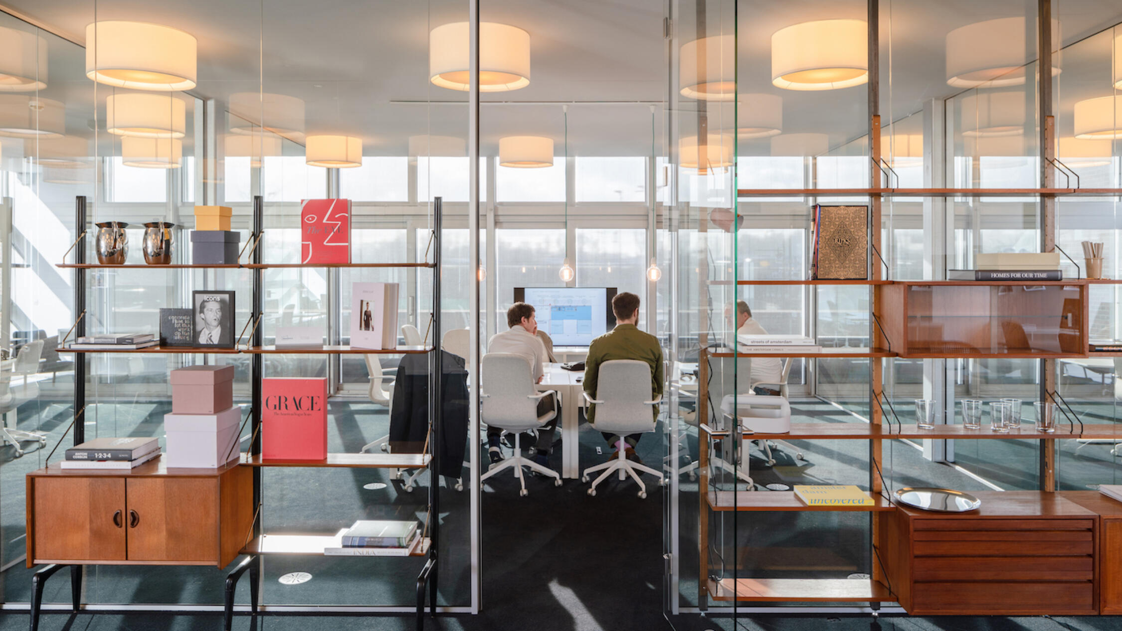 A Factorij interior office space with people working at desks framed by open bookcases