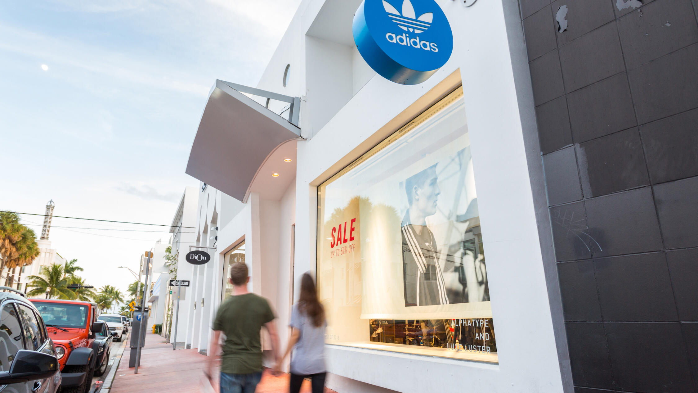 People walking by Adidas at Collins Avenue Collection