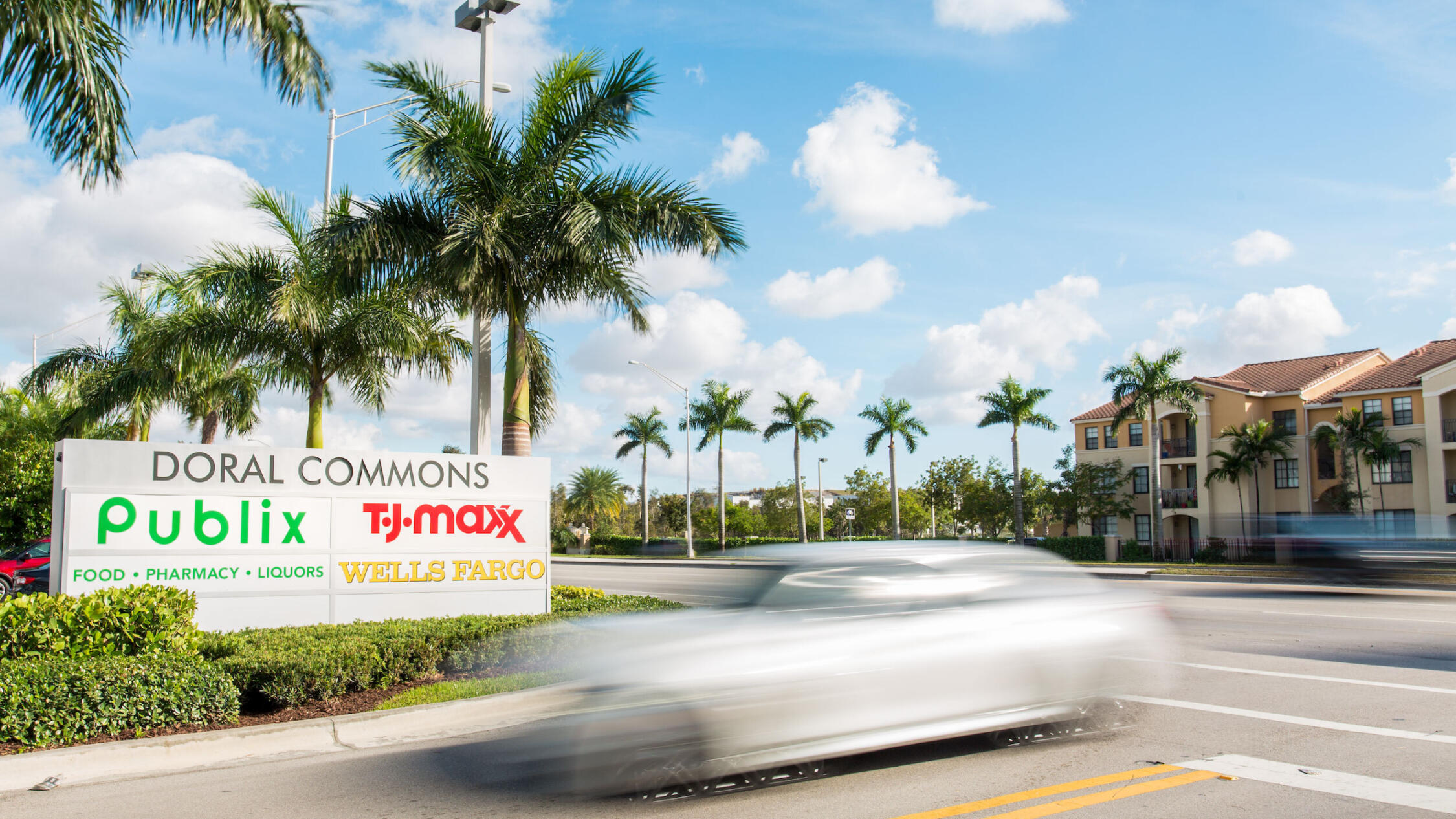 Doral Commons parking lot entrance with monument sign and street lined with palm trees