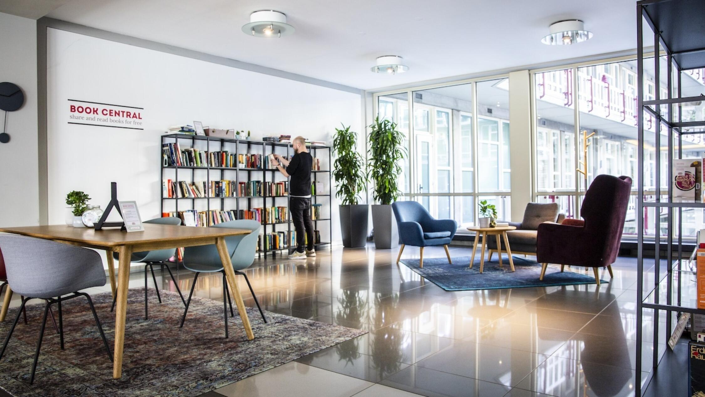 Groot Handelsgebouw interior common area with man browsing books on a shelf