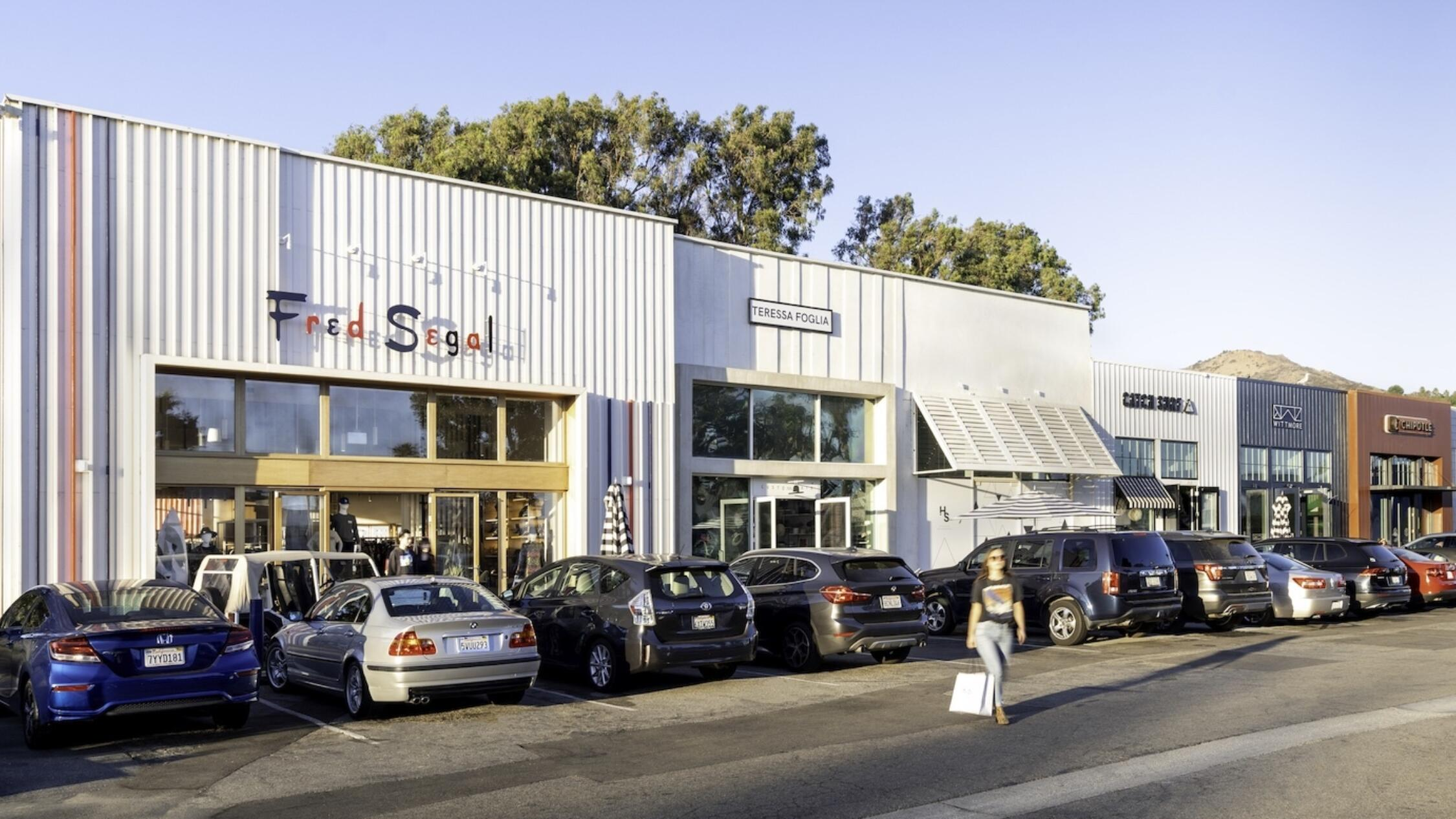 Exterior of Fred Segal at Malibu Village with shopper walking near cars parked in lot