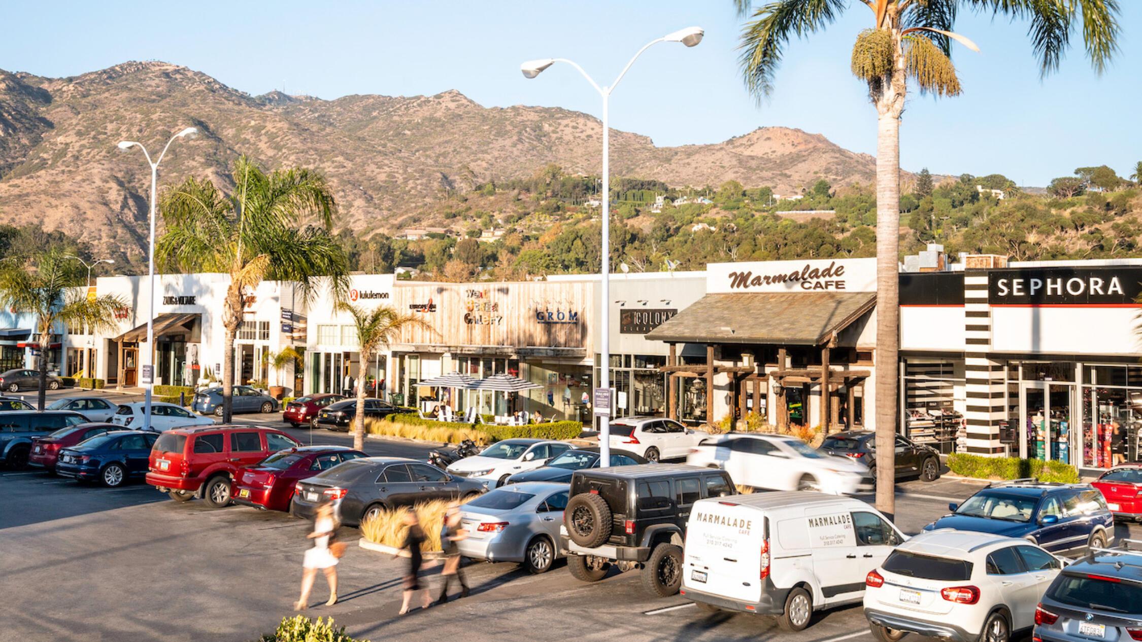 Shoppers walk through the parking lot at Malibu Village