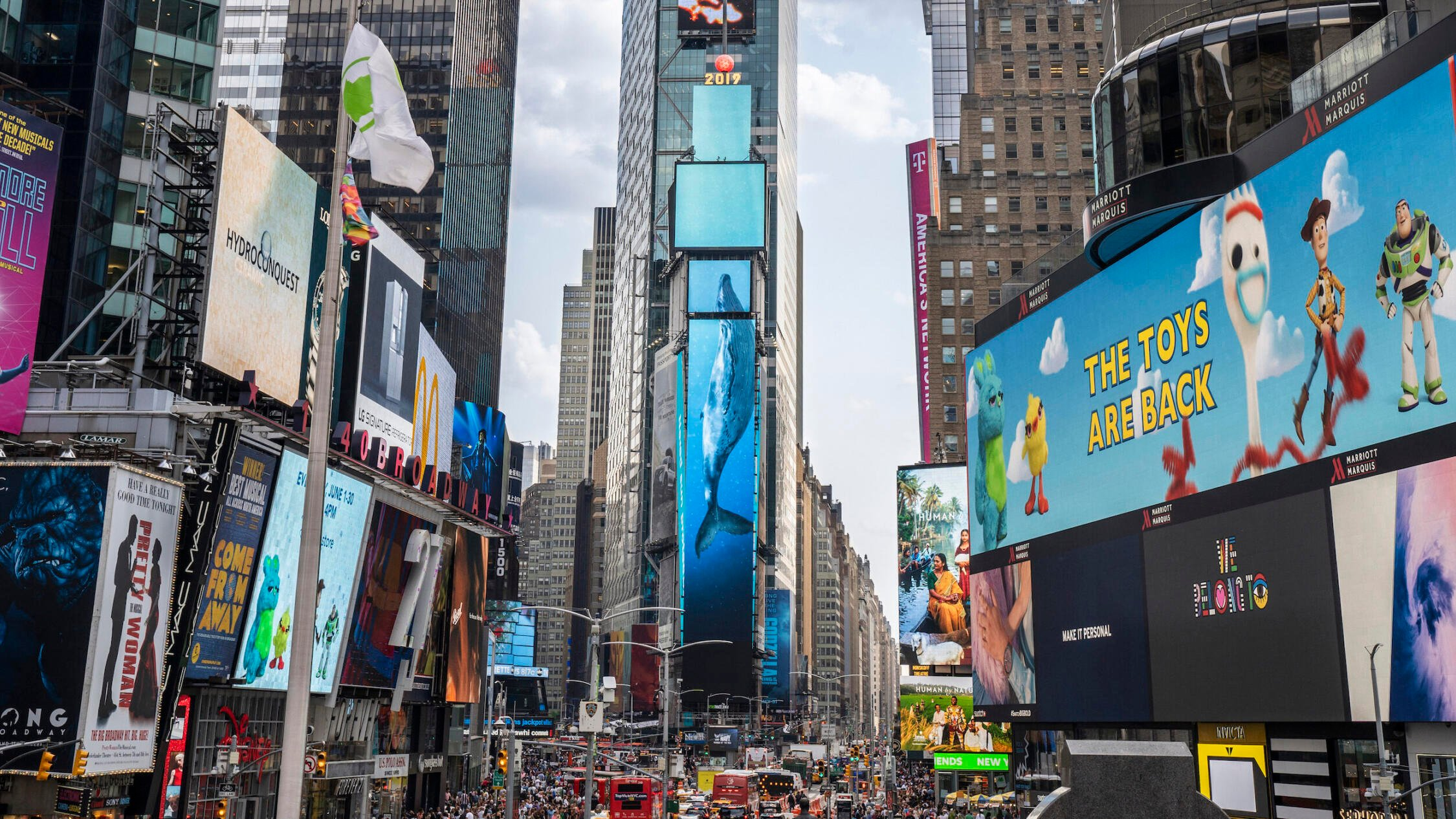 View of Times Square with One Times Square in the center. Massive animated whales are suspended on the large digital screens on One Times Square.