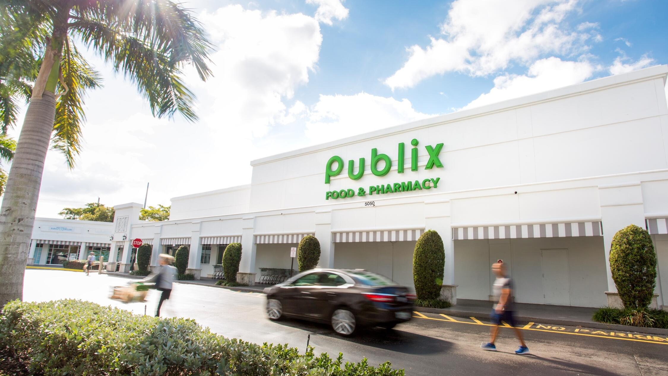People and a car moving past the Publix in Polo Club Shops with a palm tree on the left and a bright blue sky behind.