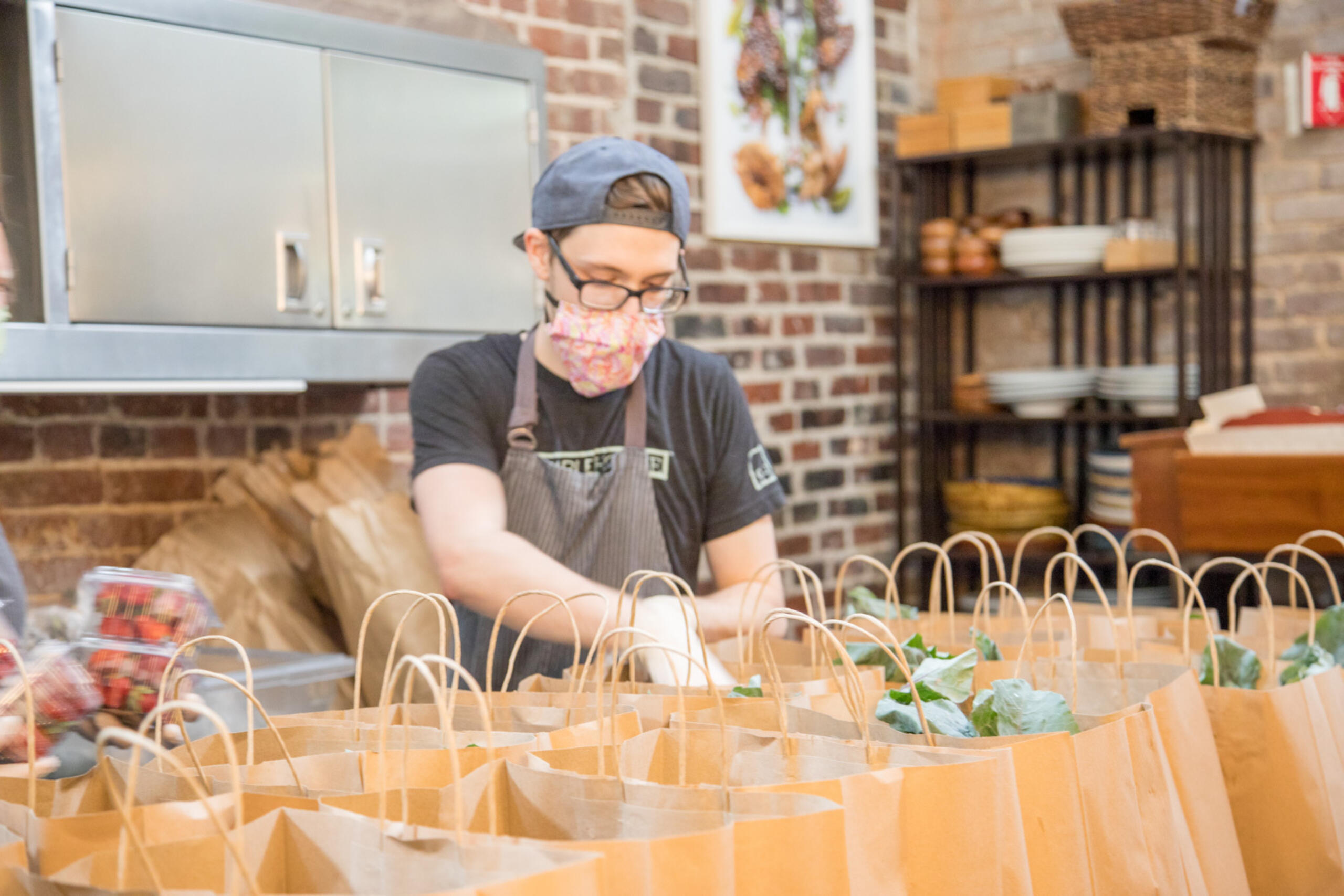 Person working in restaurant filling paper grocery bags with food for delivery