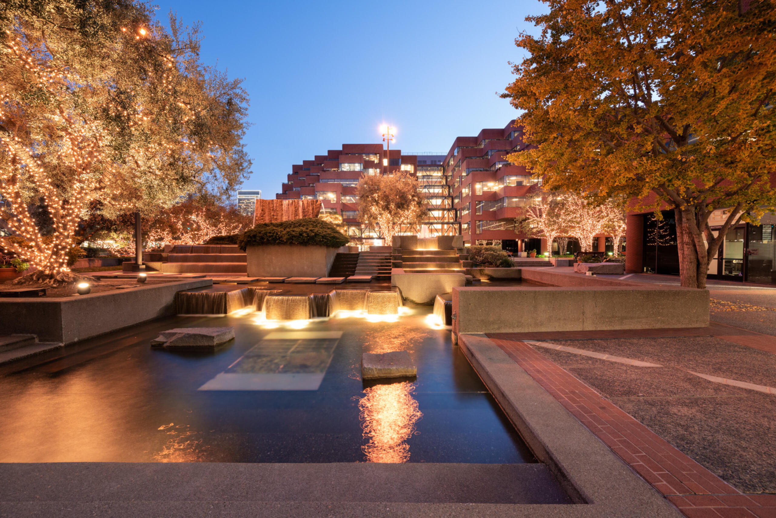Levis Plaza campus at dusk with reflecting pond in foreground and building in background