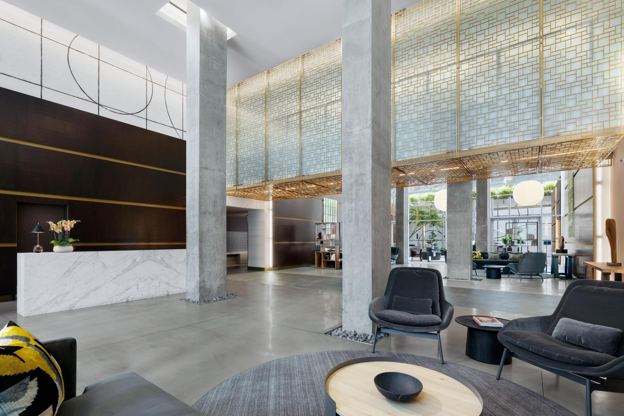 88 Leonard lobby with lounge area, concierge desk, and view of main entrance doors