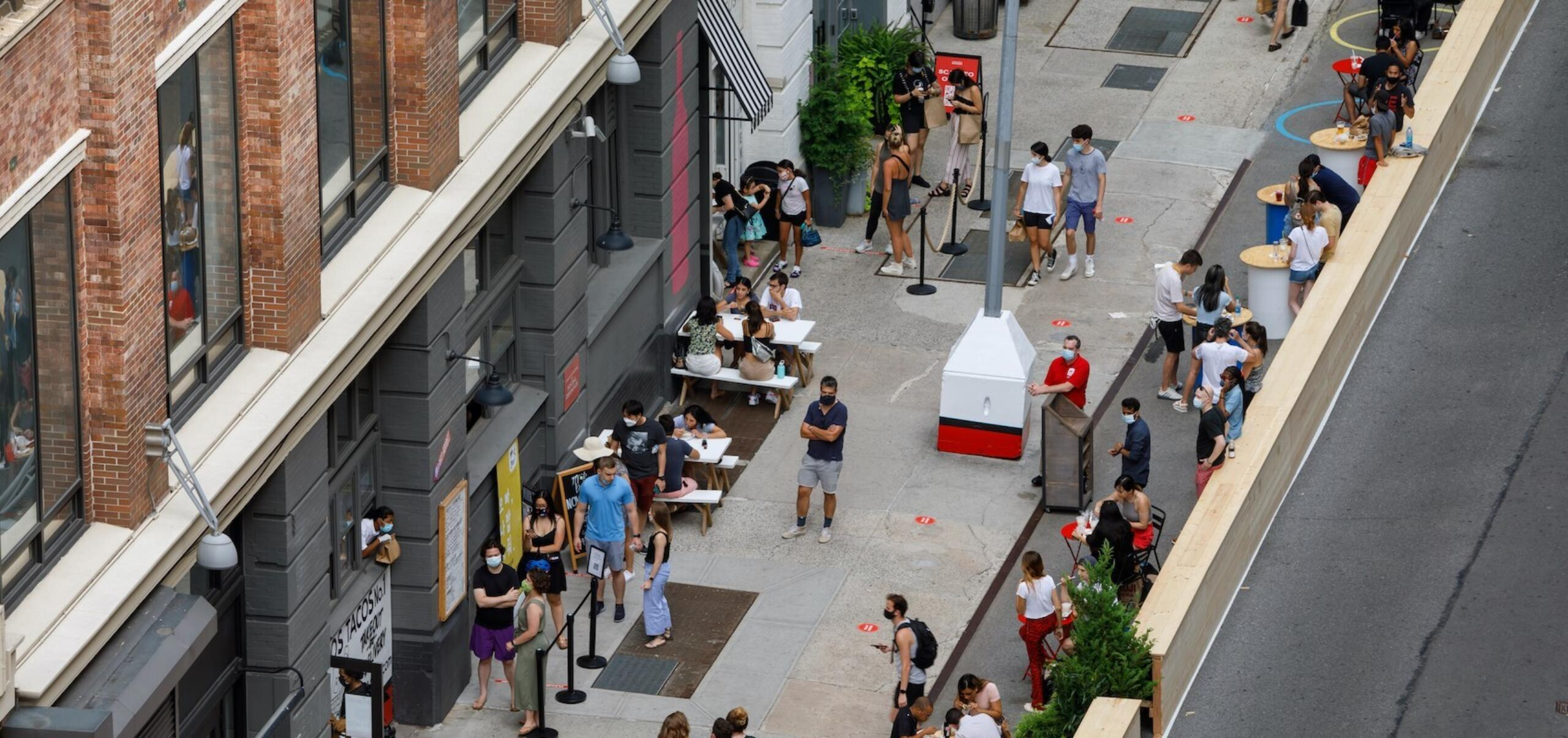 Overhead view of outdoor dining on sidewalk by Chelsea Market, with people at tables and pick-up windows