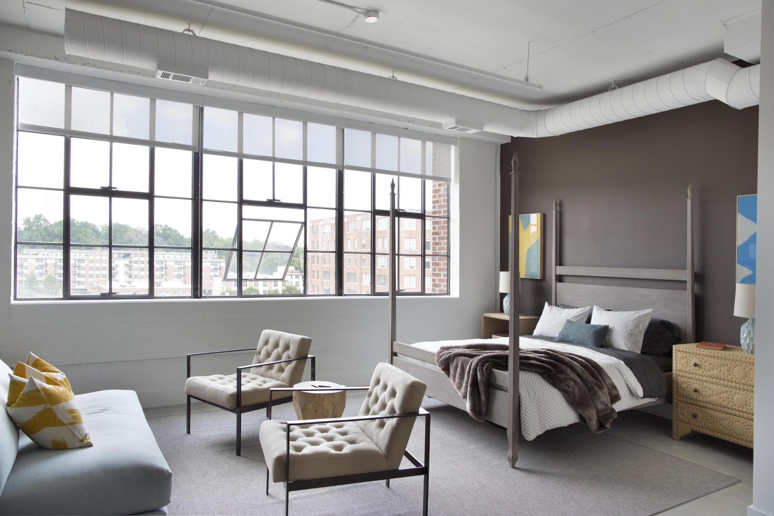 Flats at Ponce City Market bedroom interior with bed, sofa, and chairs