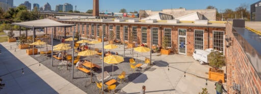 Optimist Hall outdoor courtyard with tables and chairs under umbrellas and skyline in background