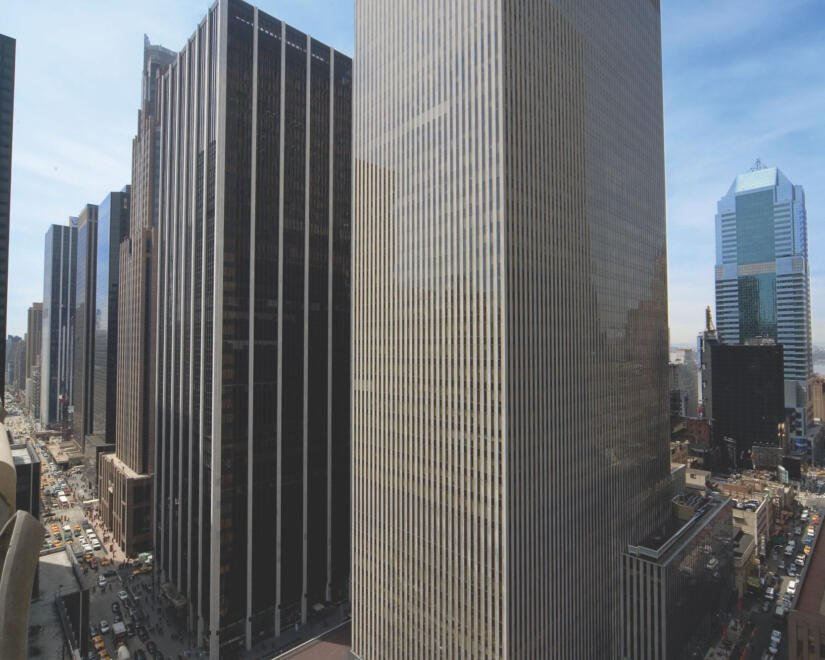 Wide exterior shot of 1211 Avenue of the Americas with traffic passing through on the streets below
