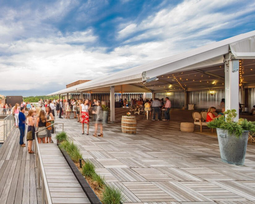 A rooftop event at Ponce City Market with people gathered under large white canopies