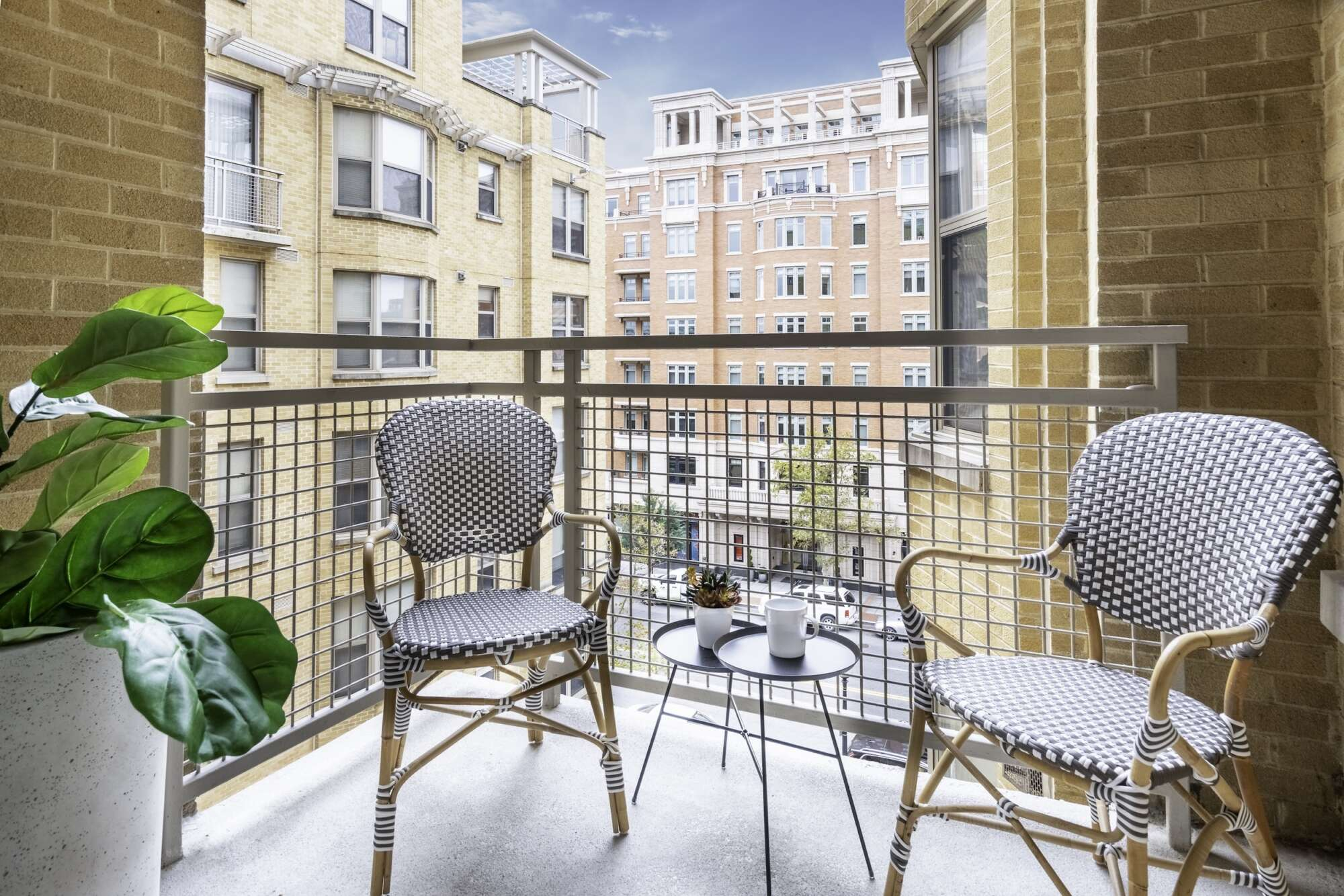 Patio of a model apartment at The Ellington with two chair and a blue sky in the distance