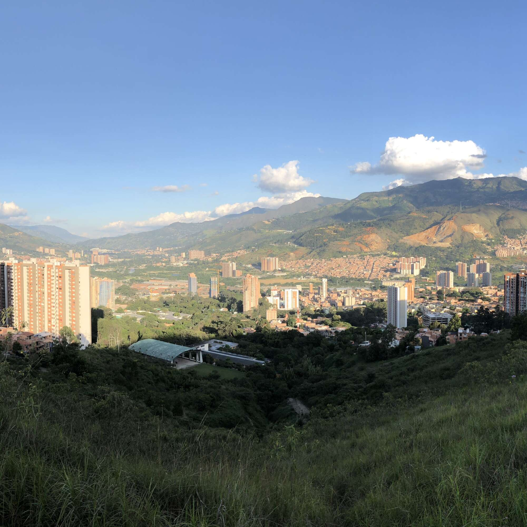 View of a green lush valley and buildings scattered throughout