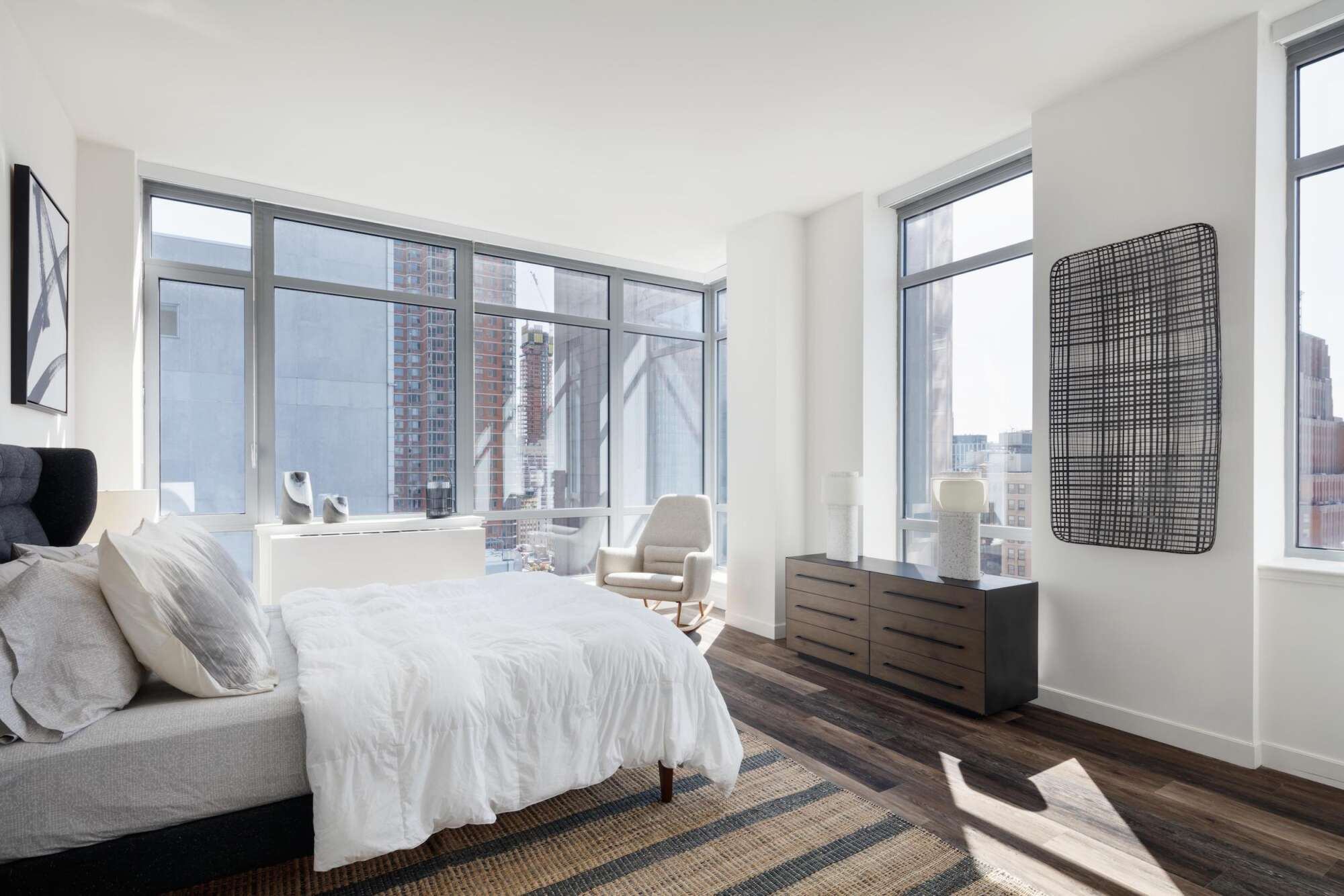 Apartment bedroom with bed, chest of drawers, and chair, with high rise buildings visible outside the windows