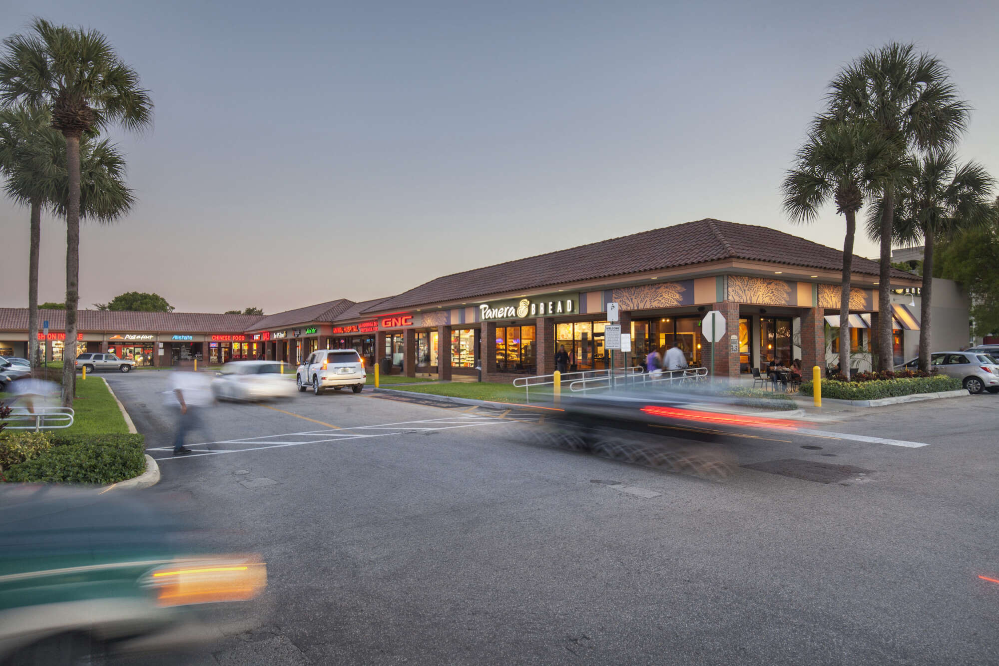 Country Club Plaza exterior with rows of shops and cars driving in parking lot