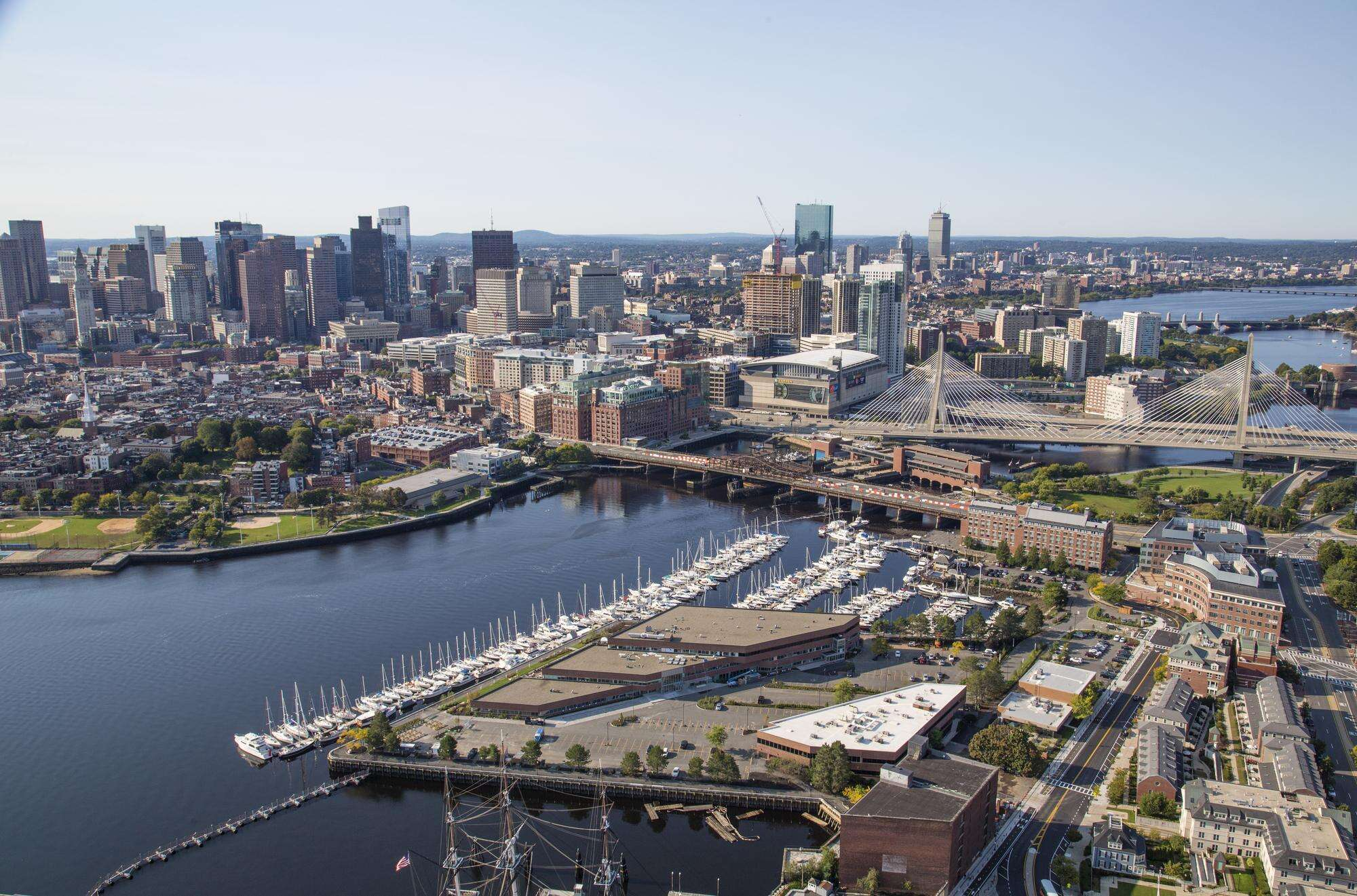 Aerial of Constitution Wharf building, marina, and river, with Boston skyline in background