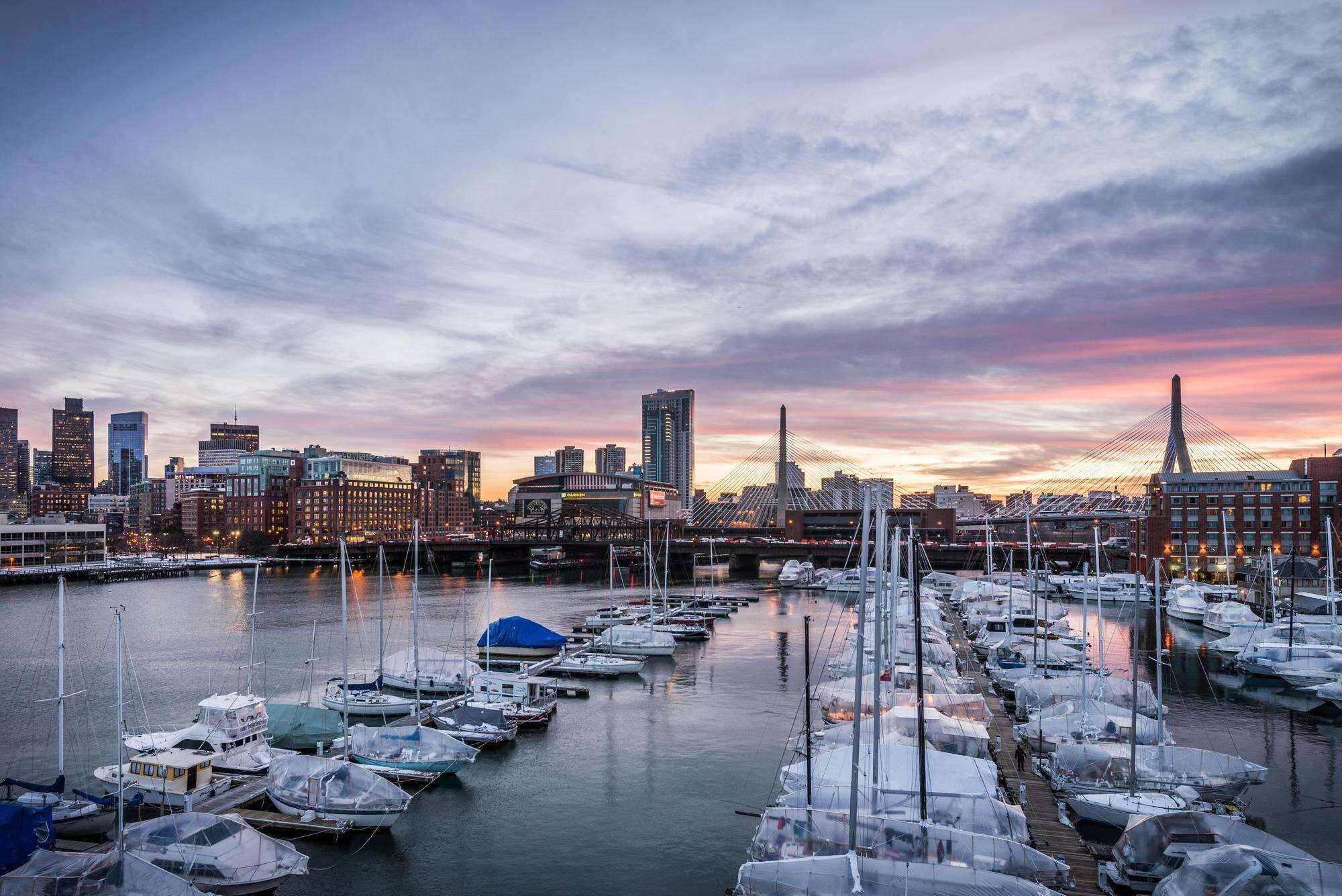 View of moored sailboats at the marina, with the Boston skyline in the background under a beautiful sunset sky
