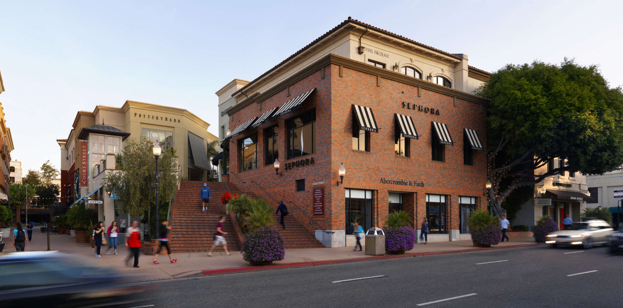 Street view of The San Luis Obispo Collection with people walking on the sidewalk and cars moving past