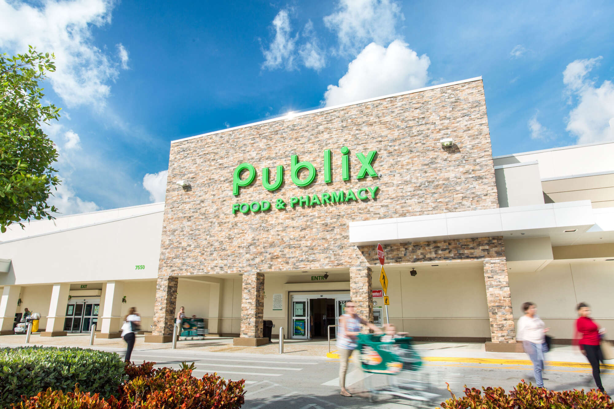 Doral Commons grocery store exterior with pedestrians crossing driveway