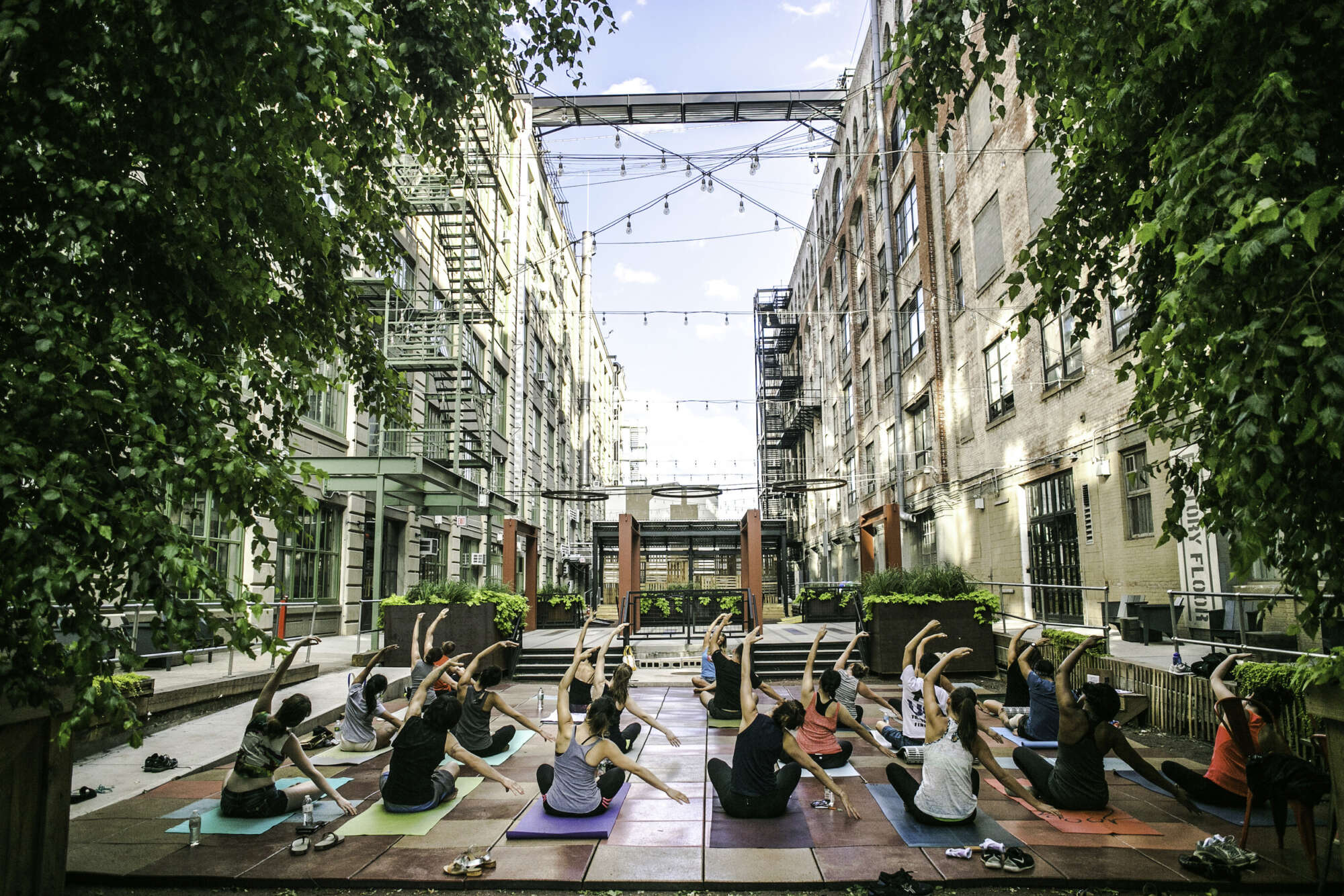 Industry City courtyard with guests practicing yoga at a class