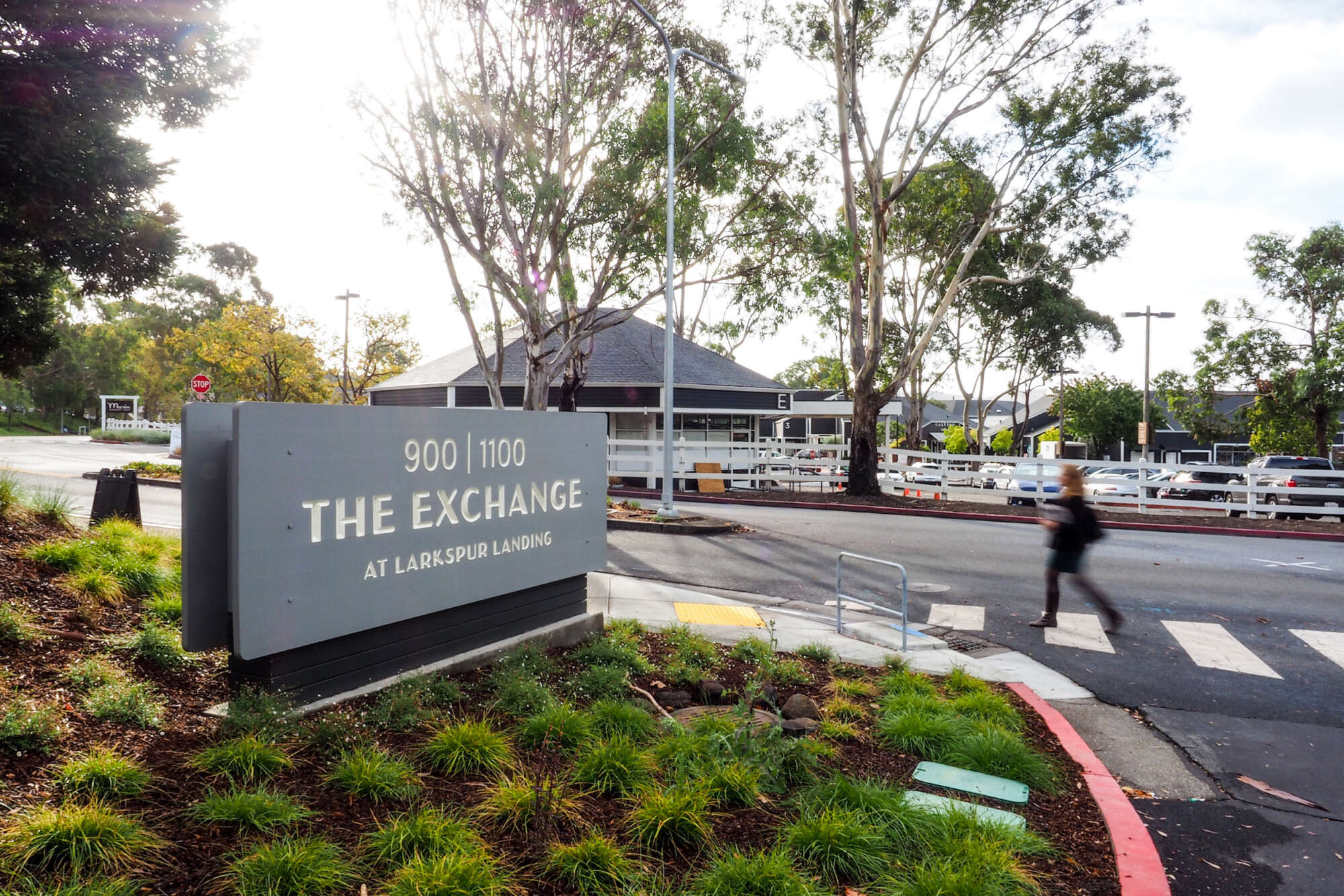 Street signage of The Exchange at Larkspur Landing with a person crossing the road nearby