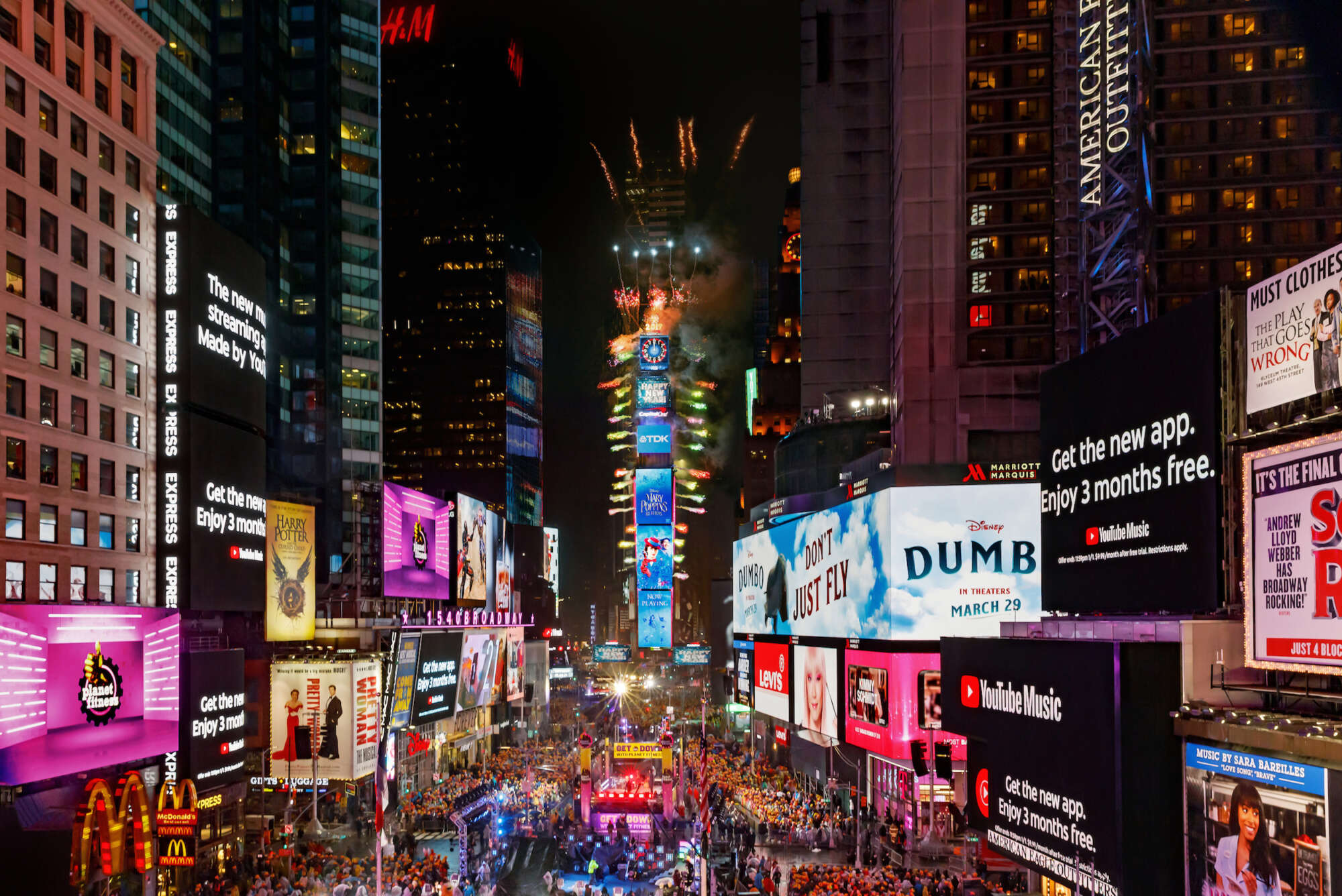 One Times Square at New Years with people in the crowd below and fireworks exploding from the building.