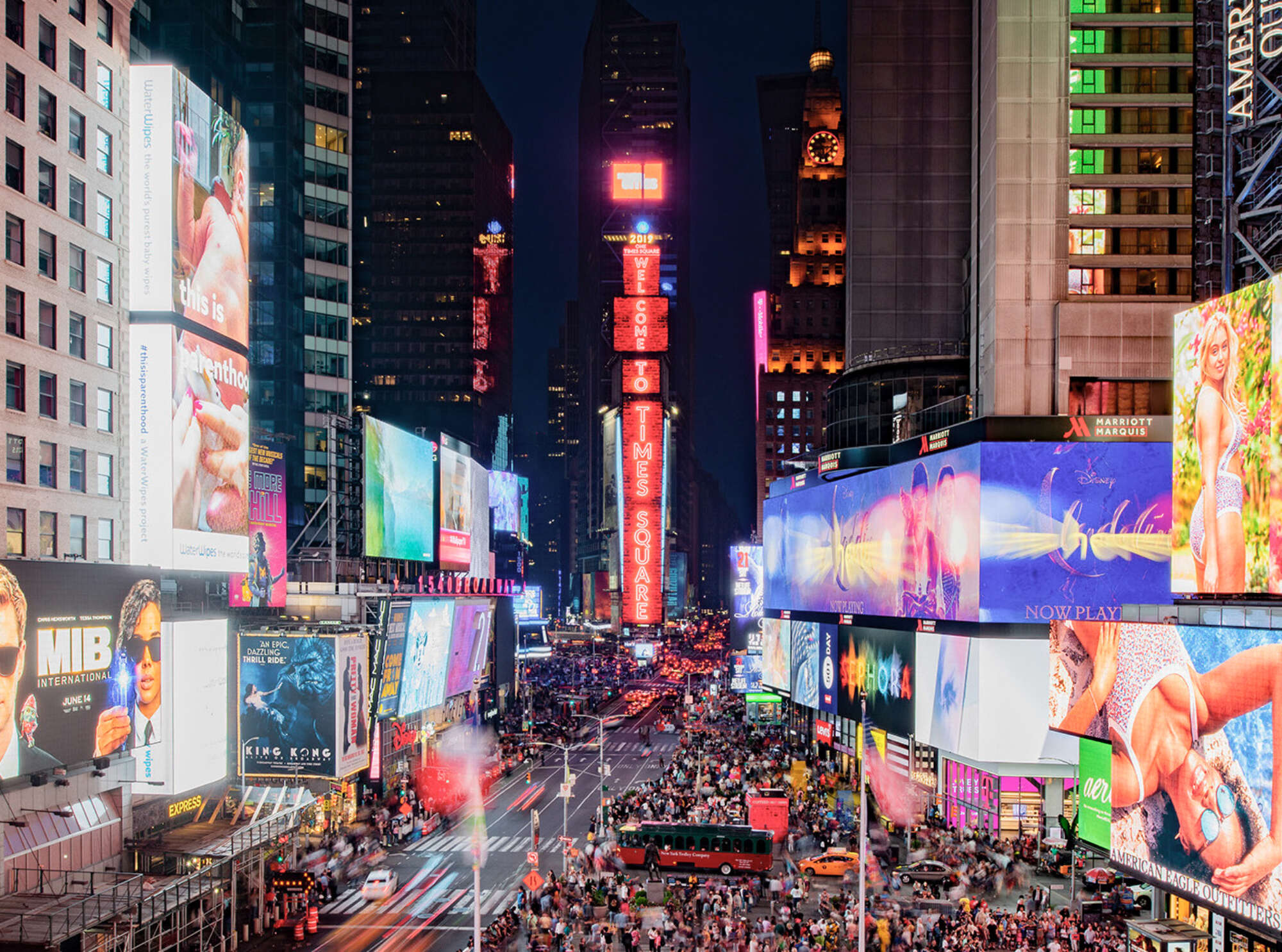 View across One Times Square from mid rise at night with throngs of pedestrians and dozens of illuminated billboards
