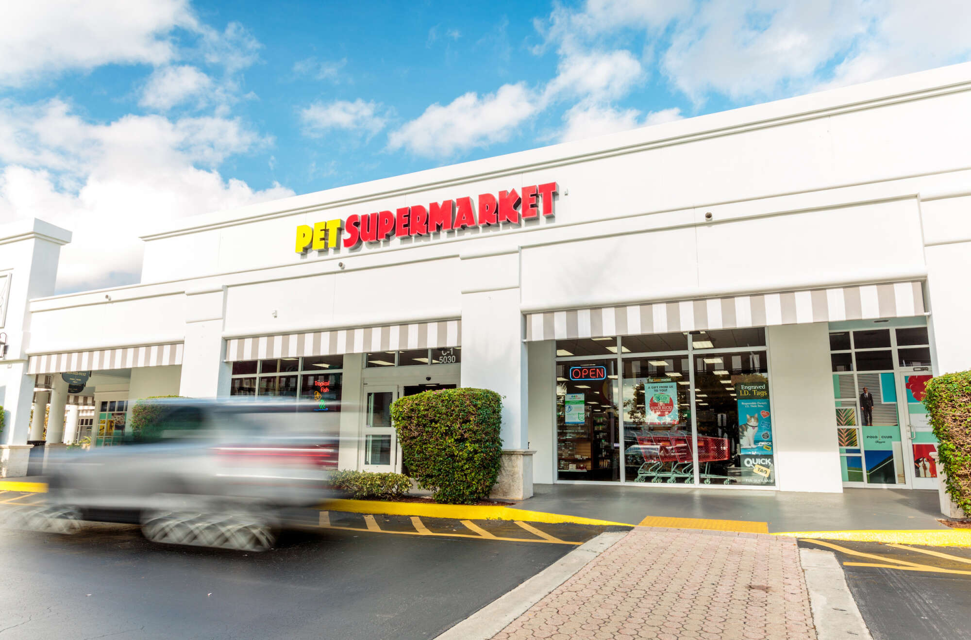 Car moving past a Pet Supermarket in Polo Club Shops