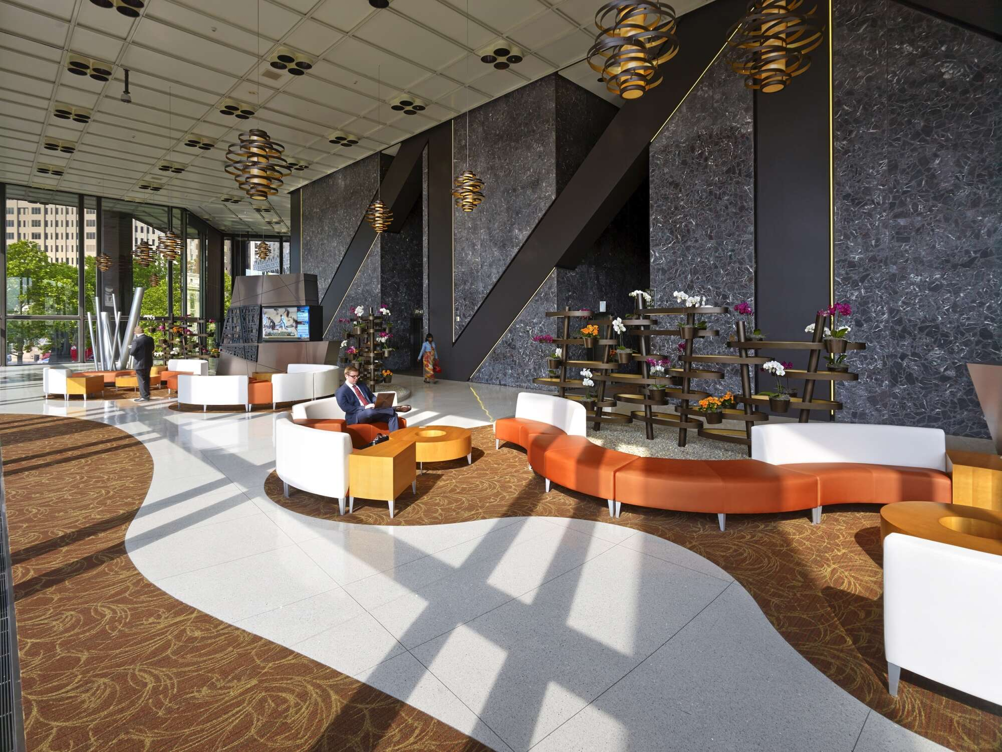 Lobby of U.S. Steel Tower with large windows, tall ceilings and curved colorful seating