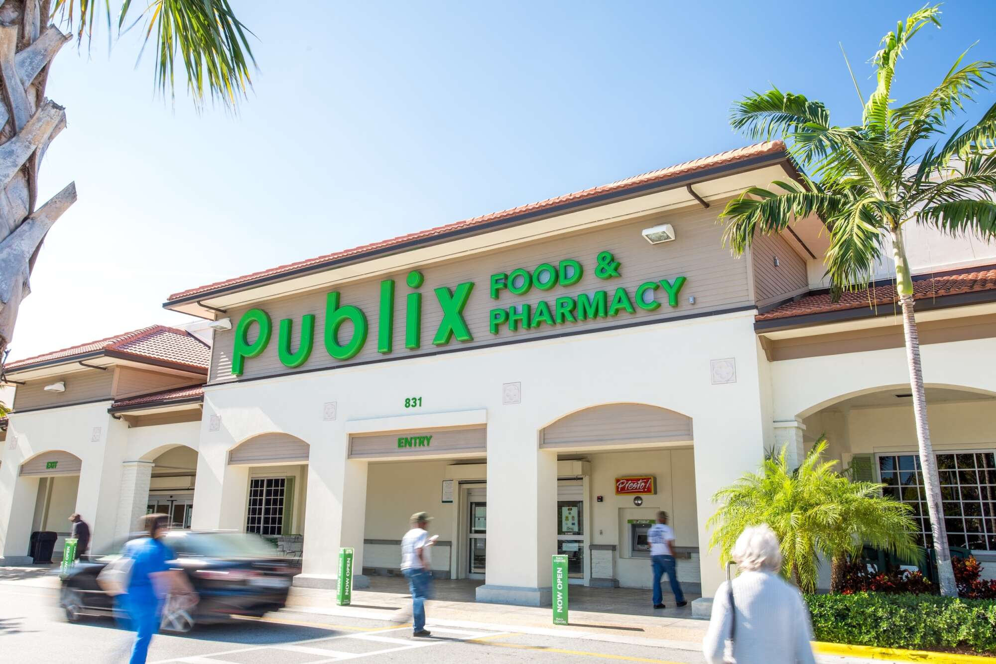 Exterior street level view of Publix grocery store at Village Commons with people and cars passing by