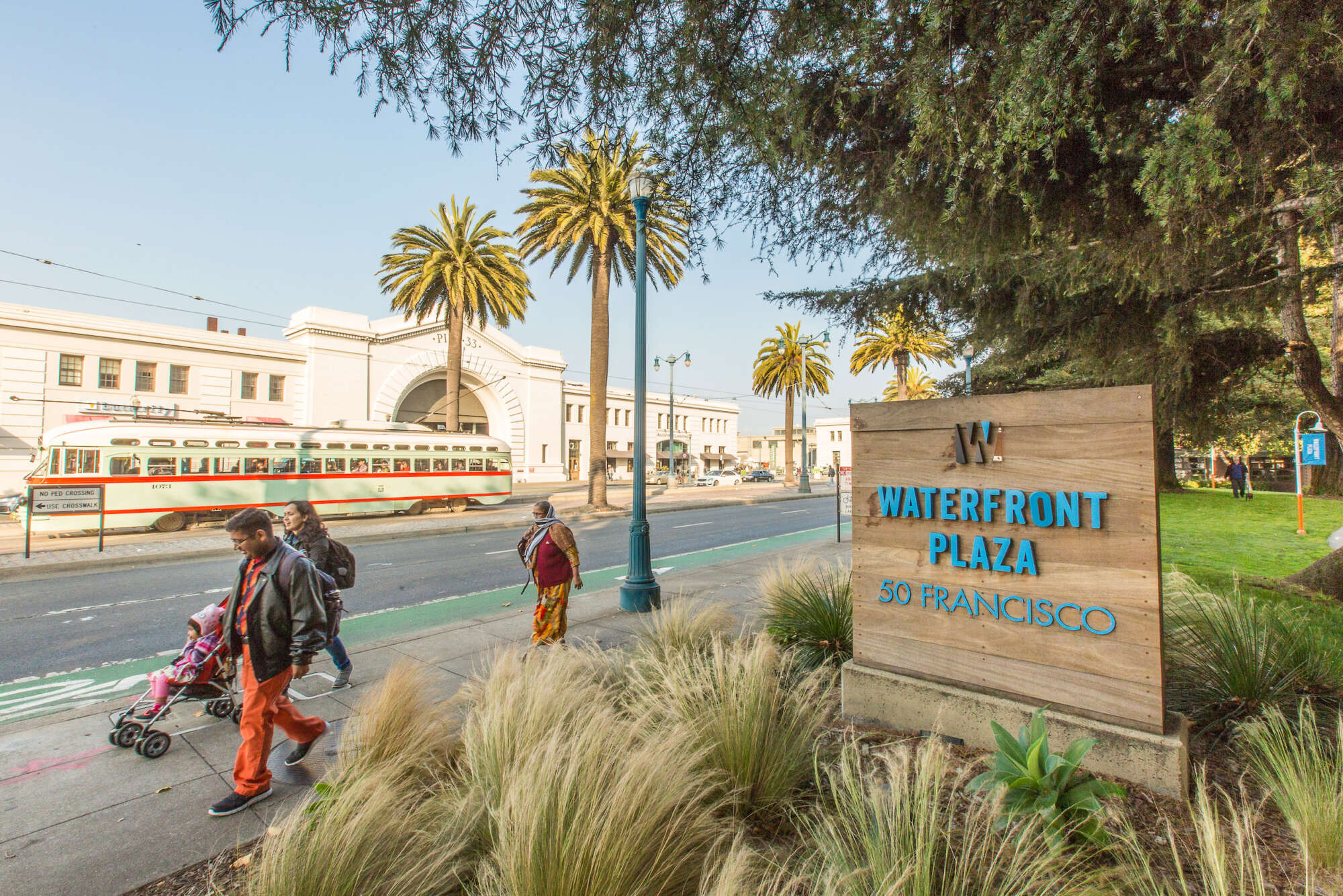 People walk by street front signage of The Waterfront Collection and a San Francisco cable car passes by