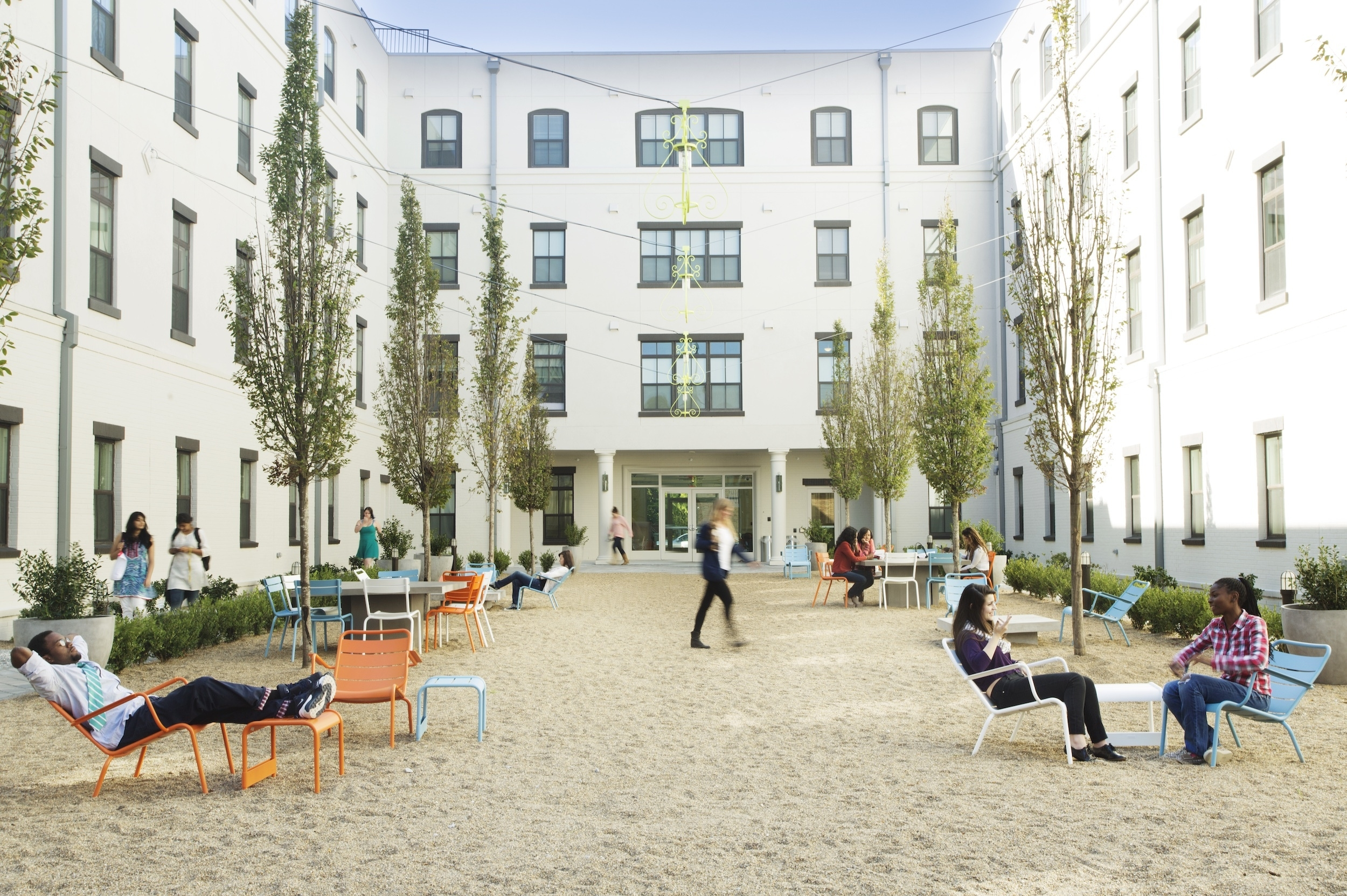 One West Victory courtyard with people seated in chairs in the sand