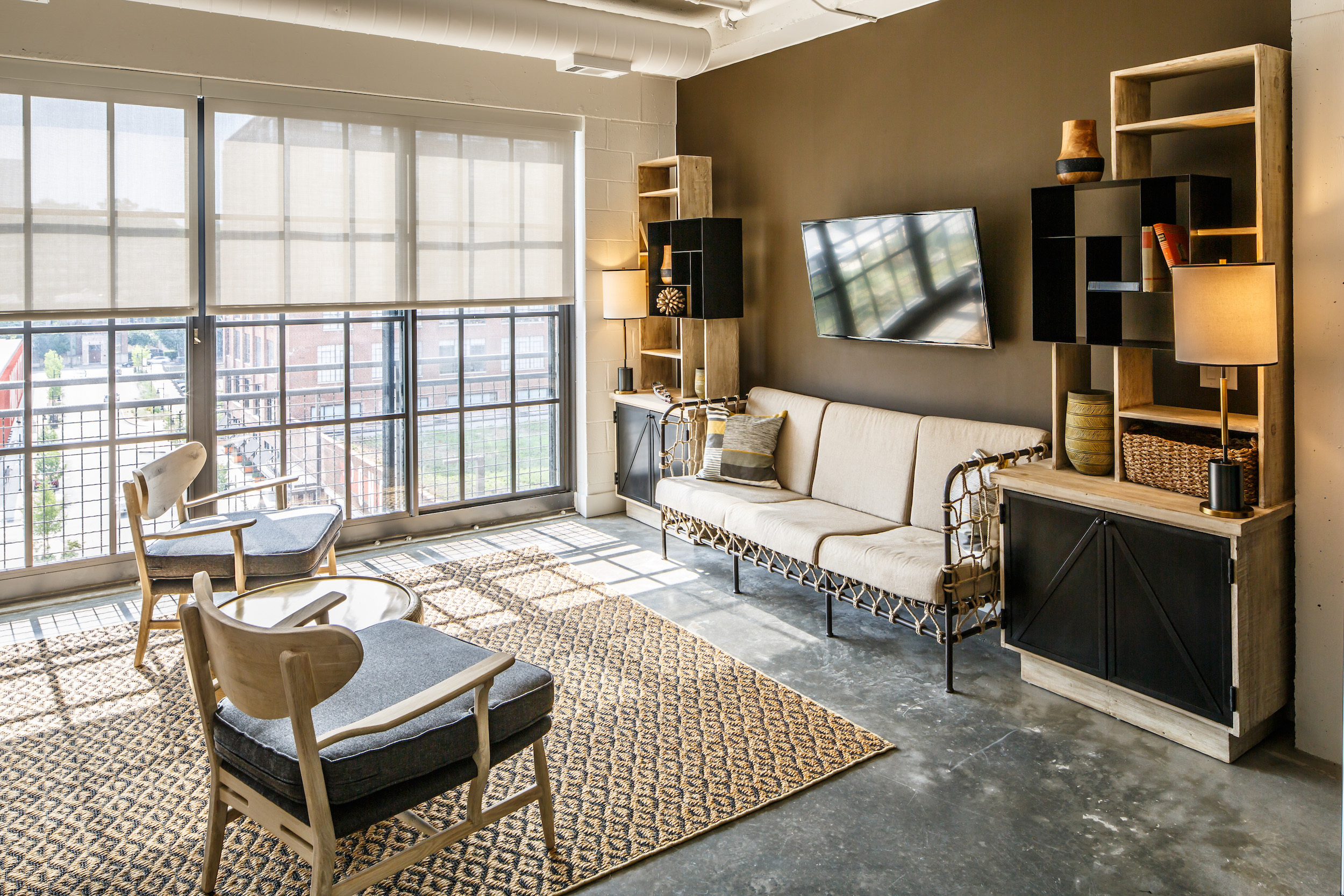 The Flats at Ponce City Market guest suite living area interior with view of building and green roof outside windows