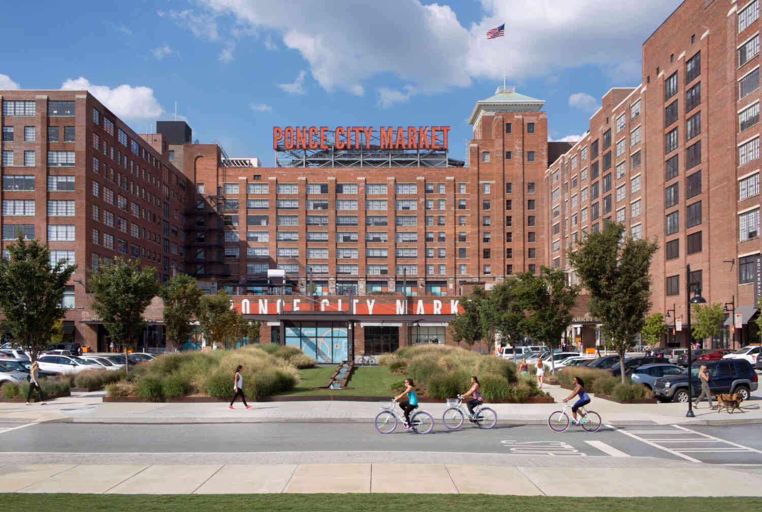 Cyclists pass by Ponce City Market under a blue sky